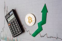 Appreciation of virtual money bitcoin. Green arrow and silver Bitcoin on paper forex chart index rating go up exchange market. Background with calculator stock photo