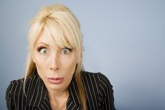 Apprehensive woman. Close Up of an Apprehensive blonde businesswoman in front of a blue background stock images