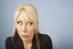 Apprehensive woman. Close Up of an Apprehensive blonde businesswoman in front of a blue background royalty free stock photo