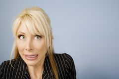 Apprehensive woman. Close Up of an Apprehensive blonde businesswoman in front of a blue background royalty free stock image