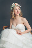Apprehensive young bride sitting thinking. Apprehensive young bride in a stylish strapless white wedding dress and veil with flowers sitting thinking looking up stock photo