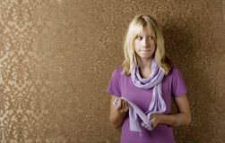 Apprehensive young girl. Leaning against a wall with gold wallpaper royalty free stock image