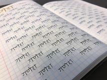 Apprenant l'alphabet hindi de devanagari sanskrit manuscrit dans le cahier image stock