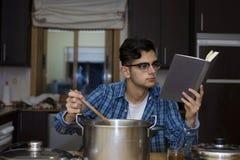 Apprendimento cucinare con il libro di cucina fotografia stock libera da diritti
