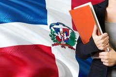 Apprendimento del concetto domenicano di lingua Condizione della giovane donna con la bandiera della Repubblica dominicana nei pr fotografia stock libera da diritti