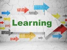 Apprendimento del concetto: freccia con l'apprendimento sul fondo della parete di lerciume Immagine Stock
