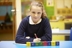 Apprendimento di parola compitato in blocchi di legno con l'allievo dietro Fotografia Stock