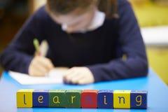 Apprendimento di parola compitato in blocchi di legno con l'allievo dietro Immagini Stock
