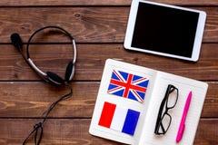Apprendimento di stile di vita inglese online sulla vista superiore del fondo di legno scuro della tavola Immagine Stock