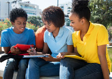 Apprendimento maschio afroamericano e delle studentesse Immagine Stock