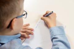 Apprendimento scrivere Il ragazzo si siede allo scrittorio ed impara scrivere con una penna in un taccuino fotografie stock