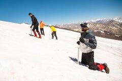 Apprendimento slittare correttamente su un pendio o su un ghiacciaio con un'ascia di ghiaccio Fotografia Stock