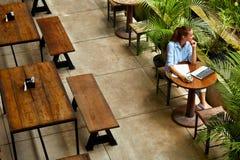 Apprendimento, studiando Donna che per mezzo del computer portatile al caffè, lavorante Fotografia Stock Libera da Diritti