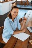 Apprendimento, studiando Donna che per mezzo del computer portatile al caffè, lavorante Fotografia Stock