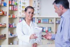 Apprendista che dà una borsa delle pillole ad un cliente Fotografie Stock