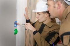 Apprendista con il cacciavite che installating gli sbocchi elettrici esterni Fotografie Stock