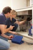 Apprendista d'istruzione dell'idraulico per riparare il dispersore di cucina Immagine Stock Libera da Diritti