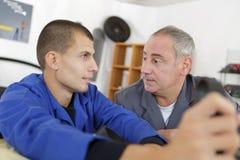 Apprendista del carpentiere che impara con il capo circa commercio Immagini Stock