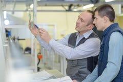 Apprendista del carpentiere che impara con l'impiegato senior Immagine Stock