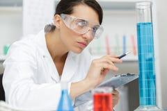 Apprendista femminile che lavora con i liquidi chimici in laboratorio fotografia stock libera da diritti