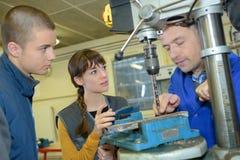 Apprendisti che lavorano alla macchina - elaborazione del metallo Fotografie Stock Libere da Diritti