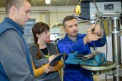 Apprendisti che lavorano alla macchina - elaborazione del metallo Immagini Stock