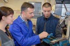 Apprendisti che lavorano alla macchina - elaborazione del metallo Immagine Stock Libera da Diritti