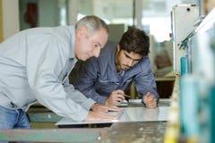 Apprendisti del carpentiere che imparano con il capo circa la misura del legno Fotografia Stock Libera da Diritti