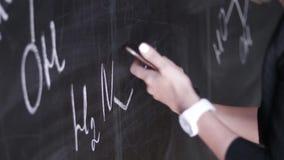 Apprenez fond sûr de tableau noir de craie de professeur de femme de formule de la science ou de chimie le beau banque de vidéos