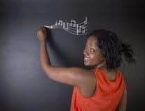 Apprenez la musique écriture de professeur ou d'étudiante sud-africaine ou d'Afro-américain de femme sur le panneau de craie photo libre de droits