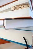 Apprenez le message écrit dans les blocs en bois entre les pages d'un livre images stock