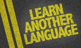 Apprenez une autre langue écrite sur la route image libre de droits