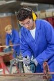 Apprenti à l'aide de la scie de circulaire dans l'atelier de métallurgie images stock