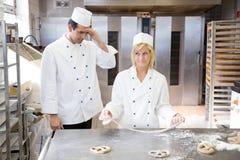 Apprenti dans la boulangerie essayant de former un bretzel hors de la pâte Photo libre de droits