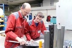 Apprenti et entraîneur à une société métallurgique - apprentissage dans le commerce photos libres de droits