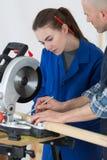 Apprenti féminin apprenant à utiliser la scie circulaire images libres de droits