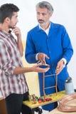 Apprenti se renseignant sur les garnitures de tuyau de cuivre avec l'instructeur photographie stock