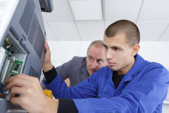 Apprentice attempting to repair computer. Apprentice attempting to repair a computer Stock Photography