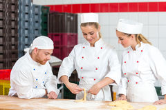 Apprentice in bakery trying to make pretzels and sceptical bakers watching Stock Photos