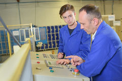 Apprentice being taught controls machine. Apprentice being taught controls of a machine Stock Photo