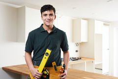Apprentice Carpenter Installing Luxury Fitted Kitchen Stock Photography