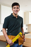 Apprentice Carpenter Installing Luxury Fitted Kitchen stock photos