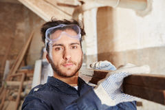 Apprentice of carpentry working. And carrying wood royalty free stock photo