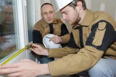 Apprentice construction man using tape measurer at site. Apprentice construction men using tape measurer at site apprentice royalty free stock images