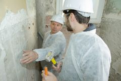 Apprentice at construction site with instructor. Apprentice stock photography