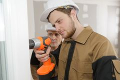 Apprentice construction worker drilling wall. Apprentice construction worker drilling a wall stock photo