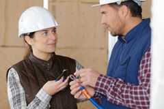 Apprentice construction worker with mentor. Female stock photo
