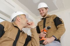 Apprentice construction worker at site with instructor. Apprentice royalty free stock photo