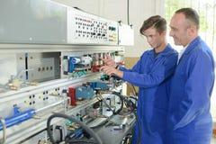 Apprentice electrician and tutor. Apprentice stock image