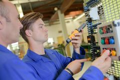 Apprentice electrician using meter. Electrician Stock Photo
